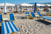 Beach umbrellas, deck chairs, tents on sand by sea — Stock Photo