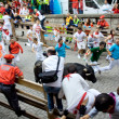 Stock Photo: PAMPLONA, SPAIN -JULY 8: Unidentified men run from bulls in