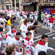 Stock Photo: PAMPLONA, SPAIN -JULY 8: Unidentified men run from bulls in stre