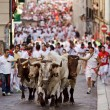 Stock Photo: PAMPLONA, SPAIN-JULY 9: Bulls and men running in street during S