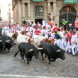 PAMPLONA, SPAIN-JULY 9: People run from bulls on street during S — Stock Photo #36484221