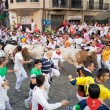 PAMPLONA, SPAIN-JULY 10: People run from bulls on street during — Stock Photo