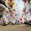 Stock Photo: PAMPLONA, SPAIN-JULY 12: People run from bulls on street during