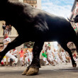 Stock Photo: PAMPLONA, SPAIN-JULY 13: Bulls and people are running in street