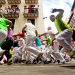 Stock Photo: PAMPLONA, SPAIN-JULY 13: People run from bulls on street