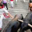 Stock Photo: PAMPLONA, SPAIN -JULY 14: Unidentified men run from bulls in str