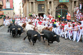 PAMPLONA, SPAIN-JULY 9: People run from bulls on street during S — Stock Photo
