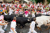 PAMPLONA, SPAIN-JULY 10: People run from bulls on street during — 图库照片
