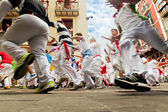 PAMPLONA, SPAIN-JULY 12: People run from bulls on street during — Stock Photo
