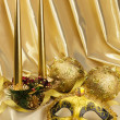 Gold mask and New Year's Christmas-tree decorations with candles on yellow fabric — Foto Stock #16839523