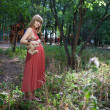 Beautiful pregnant woman in sunny park - Stock Photo