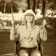 Beautiful pregnant woman sitting on a swing — Stok fotoğraf
