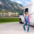 Happy young woman outside camper - Stock Photo