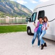 Happy young womans outside motorhome — Stock Photo #15359749