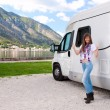 Stock Photo: Happy young woman near camper