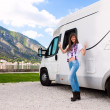 Portrait of a happy young woman standing in front of motor home - Stock Photo