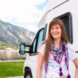 Happy young woman standing in front of camper — Stock Photo #15359781