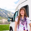 Happy young woman standing in front of camper - Stock Photo