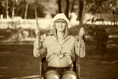 Beautiful pregnant woman sitting on a swing — Stock Photo