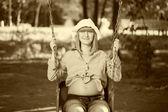 Beautiful pregnant woman sitting on a swing — Stok fotoğraf