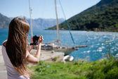Woman takin a photo of yacht — Stock Photo