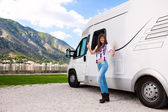Portrait of a happy young woman standing in front of motor home — Foto de Stock
