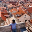Tourist looking over the roofs in Dubrovnik old town — Stock Photo #15360273