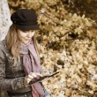 Woman with Digital Tablet in autumn forest, Sepia toning - Stock Photo