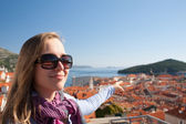 Tourist woman looking at Dubrovnik from the city walls — Stock Photo