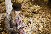 Woman with Digital Tablet in autumn forest, Sepia toning — Stock Photo