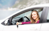 Woman with keys of new rental car — Stock Photo