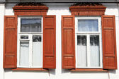 Two old windows with wooden red shutters — Stockfoto