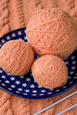 Three ball of pink yarn on a plate with asterisks and spokes for knitting — Stock Photo