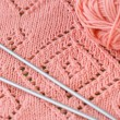 Stock Photo: Fragment of knitted blankets, pink skein of yarn and knitting needles