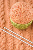 A peach-colored ball of yarn are in the national dish and needles for knitting — Stock Photo