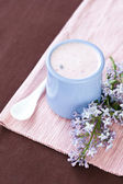 Homemade yogurt with berries in a ceramic bowl on a pink tablecloth, white spoon and a sprig of lilac — Stock Photo