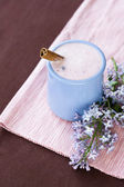 Homemade yogurt with berries in a ceramic bowl on a pink tablecloth, cinnamon stick and a sprig of lilac — Stock Photo