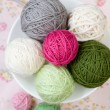 A lot of bright balls of knitting on the background of a pink flower — Stock Photo