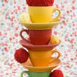 Four colorful cups and balls of yarn on a background of a red flower — Stock Photo