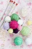 A lot of bright balls of knitting on the background of a pink flower — 图库照片