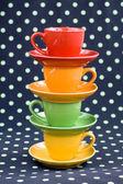 Four colorful cups on a dark background s green spots — Zdjęcie stockowe