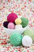 A lot of bright balls of knitting on the background of a red flower — Stock Photo