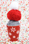 Gray, red and white ball for knitting and red Christmas cup on the background of a red flower — Stock Photo