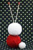 Red and white ball of yarn for knitting and needles on a dark background — Stock Photo