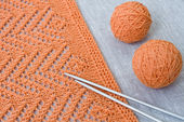Orange balls, knitted pattern and knitting needles — Stock Photo