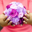 The girl in a pink dress holding a bouquet of purple flowers — Stock Photo