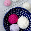 Bright balls of yarn and knitting needles on a plate — Stock Photo