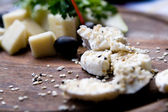 Splitting a solid tasty goat cheese with sesame seeds and herbs — Stock Photo