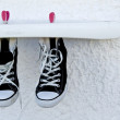 Black sneakers with white laces dry on a rope — Stock Photo