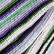 Knitting striped rug with white, purple, green and pink stripes — Stock Photo